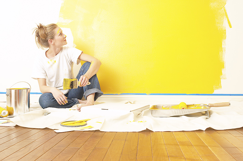 Woman painting wall in yellow.